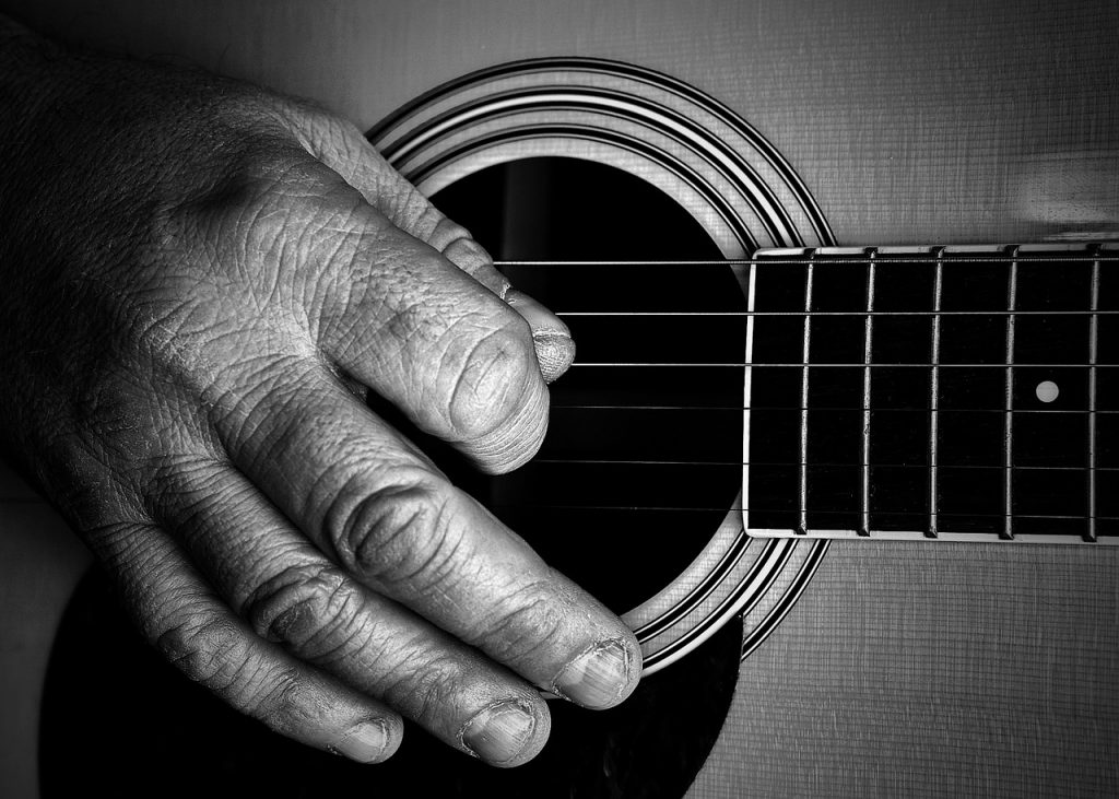 learning guitar at 50. An older mans hands picking an acoustic guitar