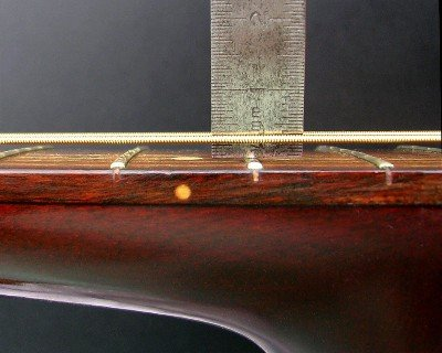steel ruler measuring the action or string height on an acoustic guitar